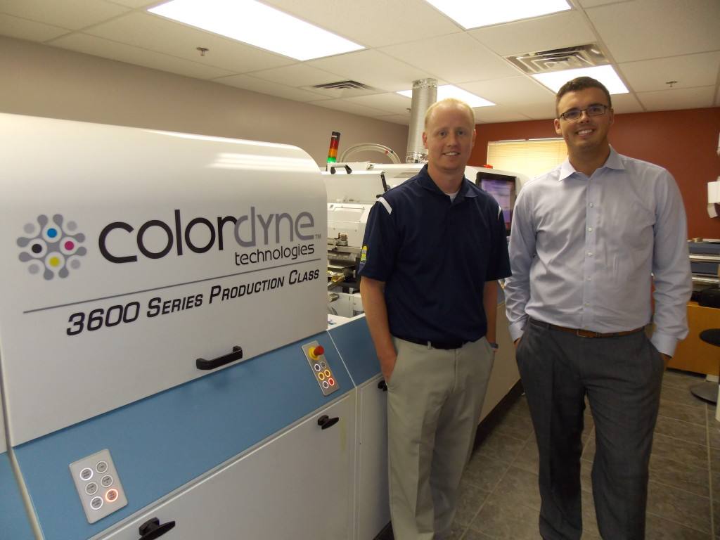 Tom Martin, project manager, Exacto, stands in front of Exacto's 3600 Series Laser Pro with Colordyne director of marketing, Taylor Buckthorpe.